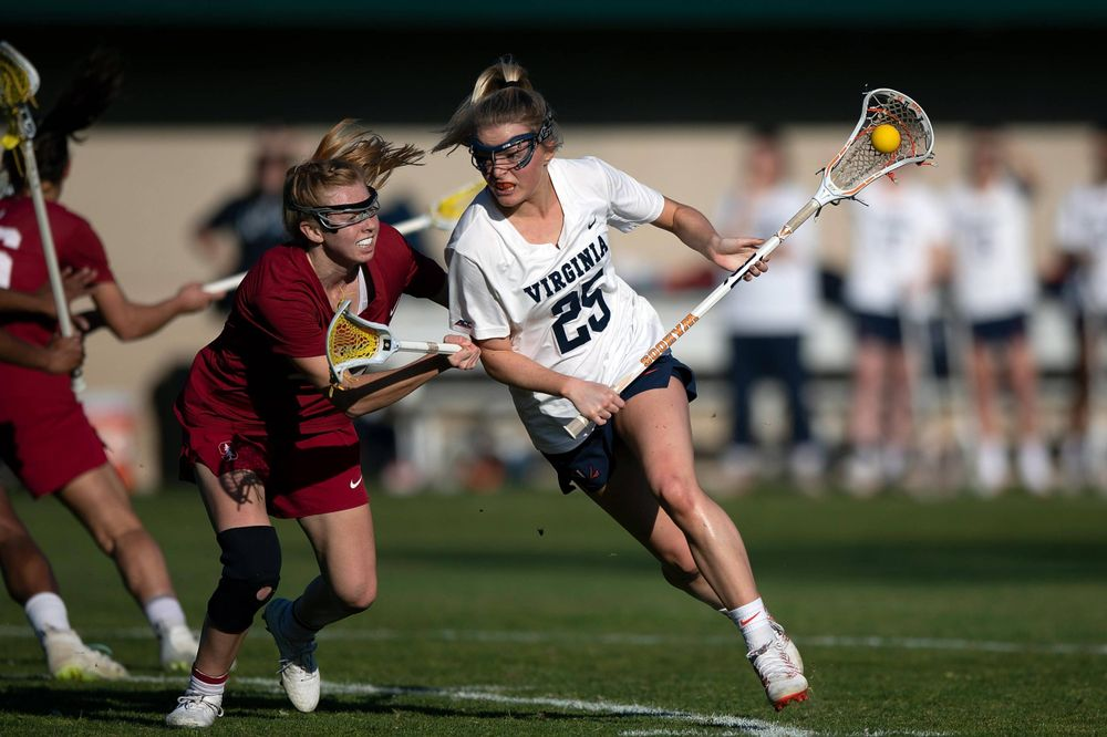 STANFORD, California - FEBRUARY 14:  Virginia Cavaliers midfield Courtlynne Caskin (25) is defended by Stanford Cardinal midfield Jacie Lemos (33) during the first half at Cagan Stadium on February 14, 2020 in Stanford, California. The Virginia Cavaliers defeated the Stanford Cardinal 12-11. (Photo by Jason O. Watson)