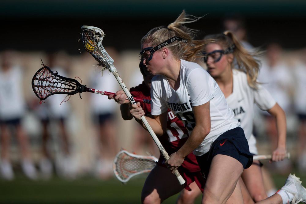 STANFORD, California - FEBRUARY 14:  Virginia Cavaliers midfield Annie Dyson (19) is defended by Stanford Cardinal defense Maggie Bellaschi (11) during the first half at Cagan Stadium on February 14, 2020 in Stanford, California. The Virginia Cavaliers defeated the Stanford Cardinal 12-11. (Photo by Jason O. Watson)